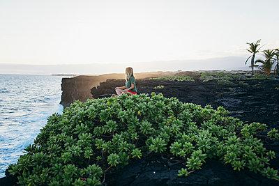 A girl is sitting on lava rocks near the ocean, Big Island, Hawaii. - p1166m2129689 by Cavan Images