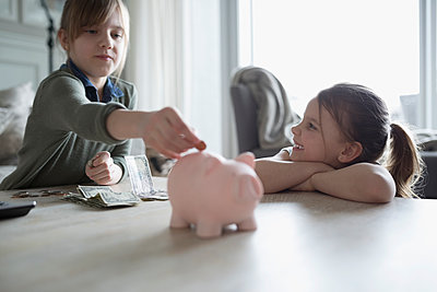 Sisters placing money in piggy bank - p1192m1231403 by Hero Images