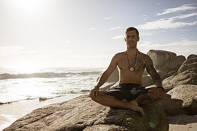 Mann meditiert auf dem Strand im Sonnenschein - p1640m2261014 von Holly & John
