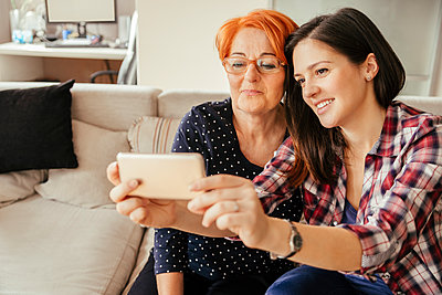Adult daughter with mother at home taking a selfie - p300m1356187 by Zeljko Dangubic