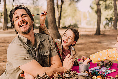 Playful girl coloring father while sitting with pine cones at picnic table in park - p300m2226021 by Eloisa Ramos