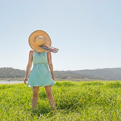 Woman standing in meadow with hat covering face - p429m1135541 by JLPH