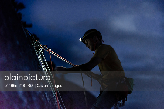 Side view man belaying climber in the night from top of Chief Squamish - p1166m2191792 by Cavan Images