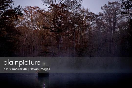 Sunrise canoe ride on foggy river. - p1166m2269646 by Cavan Images