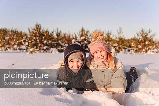 Cute siblings lying on snow against sky during sunset - p300m2265134 by Ekaterina Yakunina