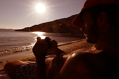 Handy am Strand - p258m2114990 von Katarzyna Sonnewend
