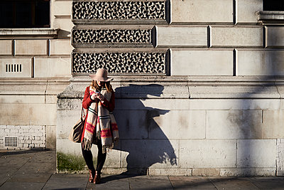 Stylish woman standing at a building using cell phone - p300m2103724 by Ivan Gener