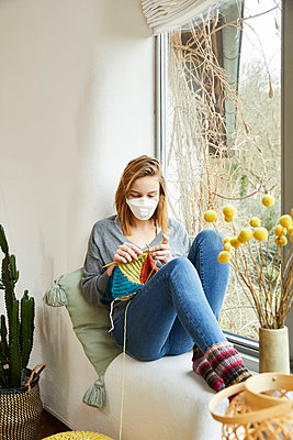 Blond woman wearing FFP2 mask and knitting at home - p300m2188591 by Sandra Bielmeier