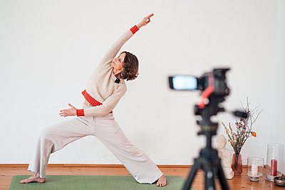 Woman filming herself while practicing Yoga at health studio - p300m2267030 by Robijn Page