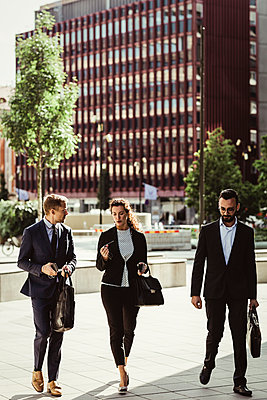 Entrepreneur discussing strategy with male and female colleagues while walking outdoors - p426m2169598 by Maskot