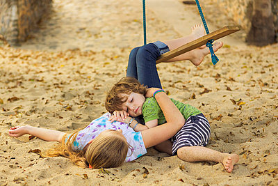 Caucasian boy laying on chest of sister at beach - p555m1305351 by Marc Romanelli