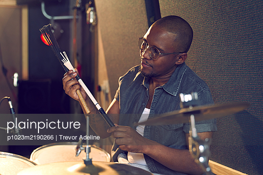 Male drummer with drum brush in recording studio - p1023m2190266 by Trevor Adeline
