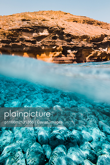 Diving under a yellow mountain in summer - p1166m2131356 by Cavan Images