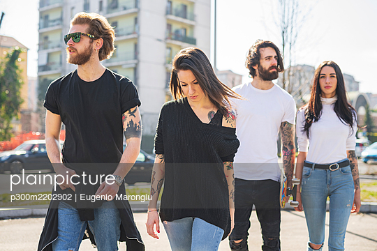 Stylish friends walking in city on sunny day - p300m2202902 by Eugenio Marongiu