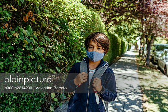 Schoolboy wearing mask looking away while standing by plants on footpath - p300m2214200 by Valentina Barreto