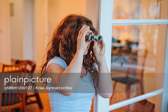 Junge Frau blickt durch ein Fernglas - p586m1200127 von Kniel Synnatzschke