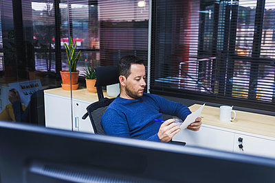 Bearded Man looking at chart in office - p1166m2138119 by Cavan Images