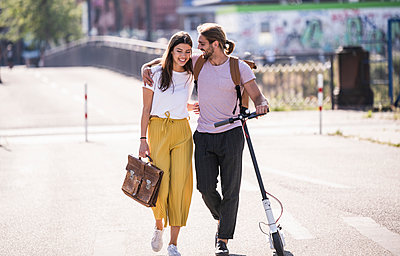 Young couple with electric scooter walking on the street - p300m2132612 by Uwe Umstätter