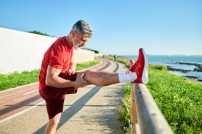 Mature man stretching leg on wooden railing by the sea during sunny day - p300m2275599 by Kiko Jimenez
