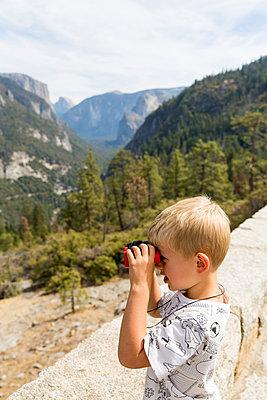 Blonde boy watching mountain landscape through binoculars - p756m2125044 by Bénédicte Lassalle