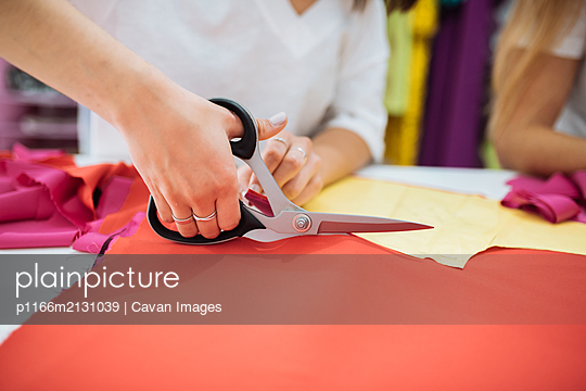 hands with scissors cutting a cloth - p1166m2131039 by Cavan Images