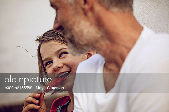 Portrait of smiling girl with popsicle looking at her father, Cape Town, Western Cape, South Africa - p300m2155589 by Maya Claussen