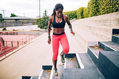 Full length of sportswoman exercising on steps at stadium - p1166m1086167f by John Trice