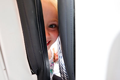 little girl smiling and looking at camera between seats on airplane - p1166m2157143 by Cavan Images