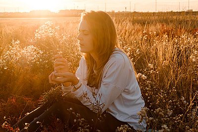 Portrait of a woman with long hair is sitting at field among flowers - p1363m2038080 by Valery Skurydin