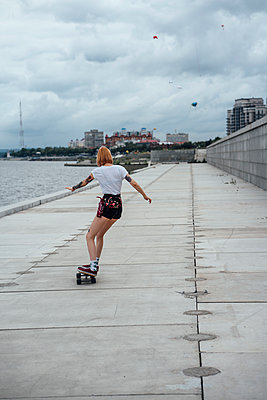 Rear view of young woman riding carver skateboard at the riverside - p300m2059649 by Vasily Pindyurin