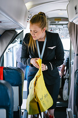 Air stewardess holding life jacket while standing in passenger cabin - p426m1542696 by Helena Wahlman