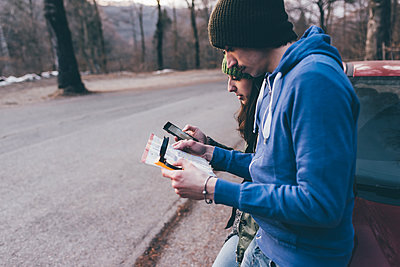 Hiking couple looking at map and smartphone on forest roadside, Monte San Primo, Italy - p429m1447972 by Eugenio Marongiu