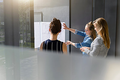 Colleagues discussing plans on glass wall - p429m2058466 by suedhang photography