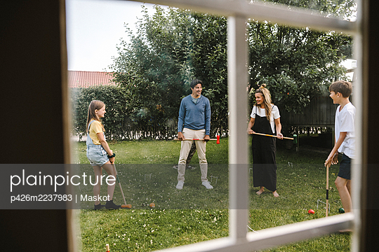 Happy family playing polo in front yard - p426m2237983 by Maskot