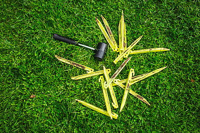 A mallet and yellow plastic pegs, tent pegs on the grass, camping equipment.  - p1100m1522534 by Mint Images