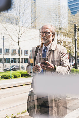 Mature businessman with cell phone and takeaway coffee in the city - p300m1587855 von Uwe Umstätter