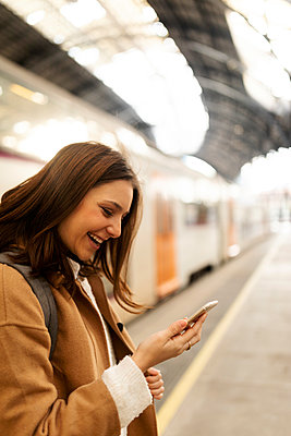 Happy young woman using cell phone at the train station - p300m2160325 by Valentina Barreto