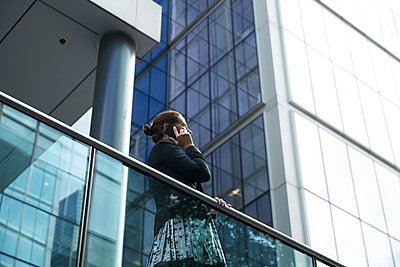 Businesswoman talking on mobile phone while standing by railing against building - p300m2227082 by Pete Muller