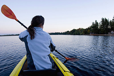 Woman kayaking on Lake Ossipee - p3437405f by Justin Bailie