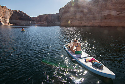 Woman looking at map while sitting on paddleboard, Lake Powell, Utah, USA - p343m1578140 by Suzanne Stroeer