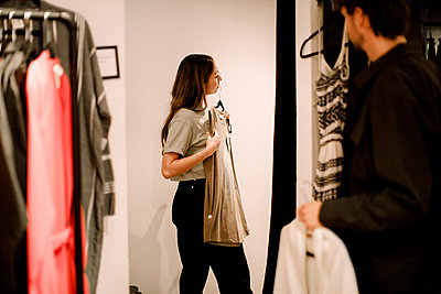 Side view of woman with clothing in retail store - p426m2213164 by Maskot