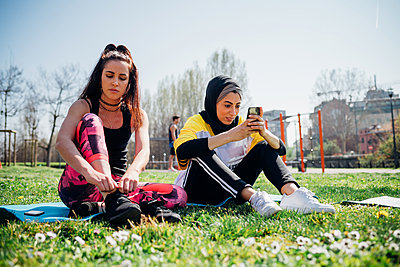 Calisthenics class at outdoor gym, young women sitting on grass tying laces and looking at smartphone - p429m2098441 by Eugenio Marongiu