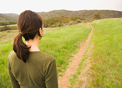 Mixed Race woman standing on path in field - p555m1491124 by PBNJ Productions