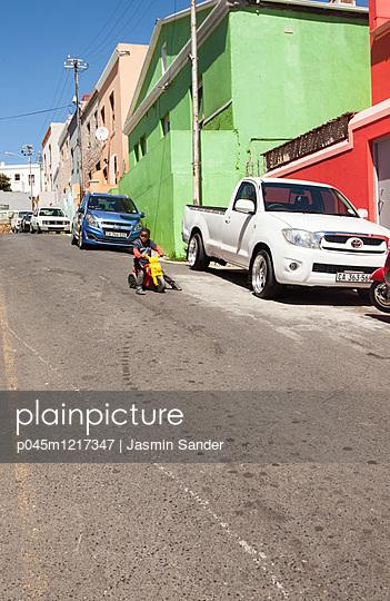 Afrikanischer Junge fährt auf Roller - p045m1217347 von Jasmin Sander