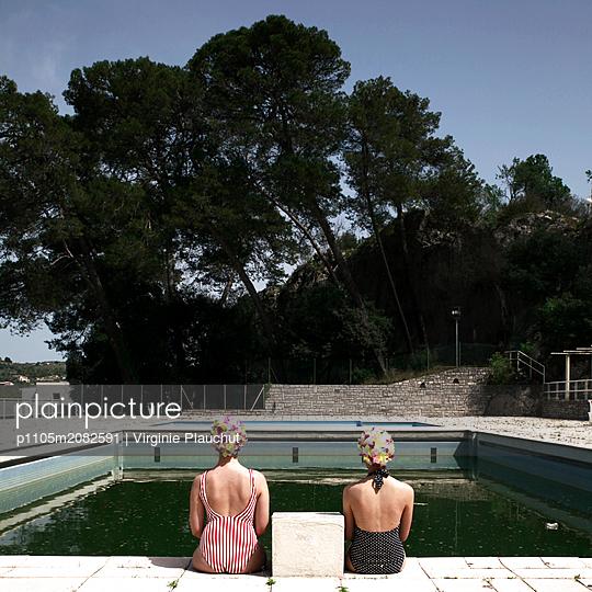 Zwei Freundinnen sitzen am Beckenrand - p1105m2082591 von Virginie Plauchut