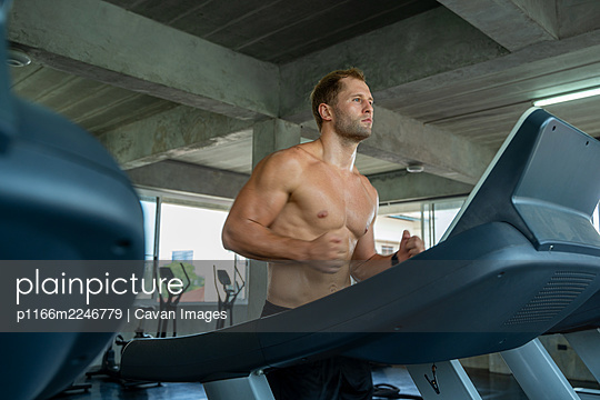 Fitness man are running on modern electric treadmills at the gym - p1166m2246779 by Cavan Images
