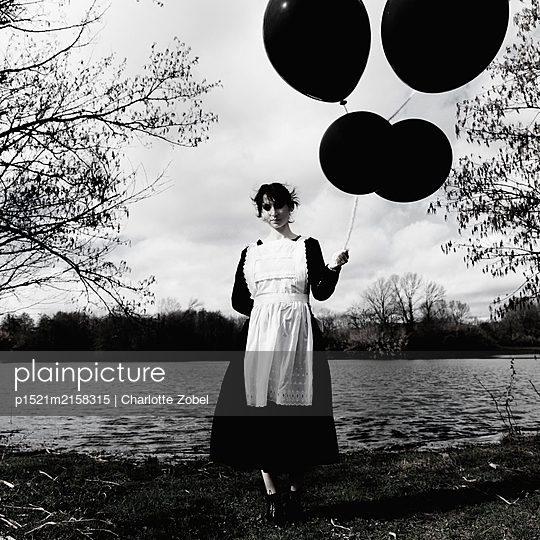 Maid holding black balloons - p1521m2158315 by Charlotte Zobel