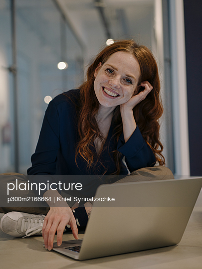 Portrait of smiling redheaded woman using laptop on the floor - p300m2166664 by Kniel Synnatzschke