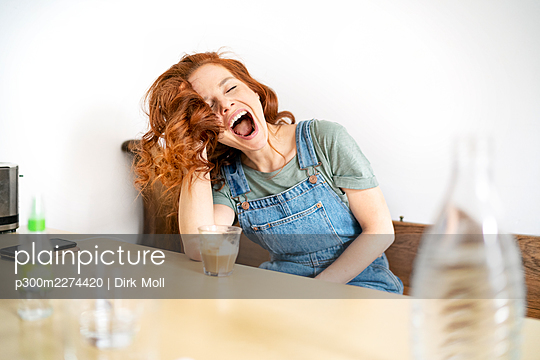 Beautiful mid adult redhead woman sitting with mouth open and eyes closed at table - p300m2274420 by Dirk Moll