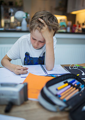 Focused boy home schooling at table - p1023m2201363 by Paul Bradbury